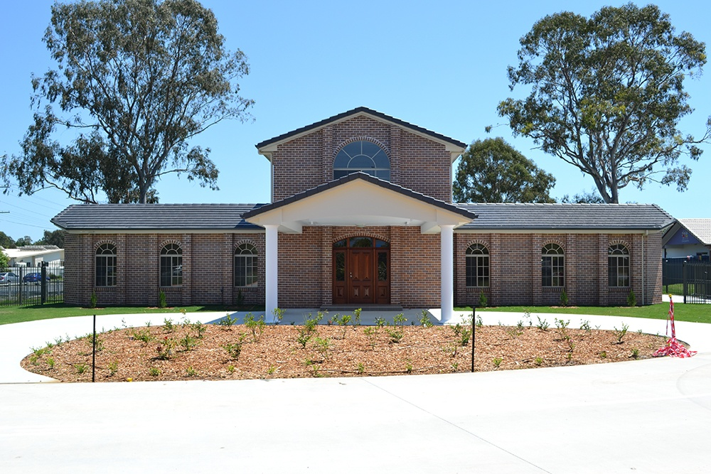 Two level red brick Bishop's Manse with drive-up entrance and arch windows at Greek Orthodox Archdiocese.