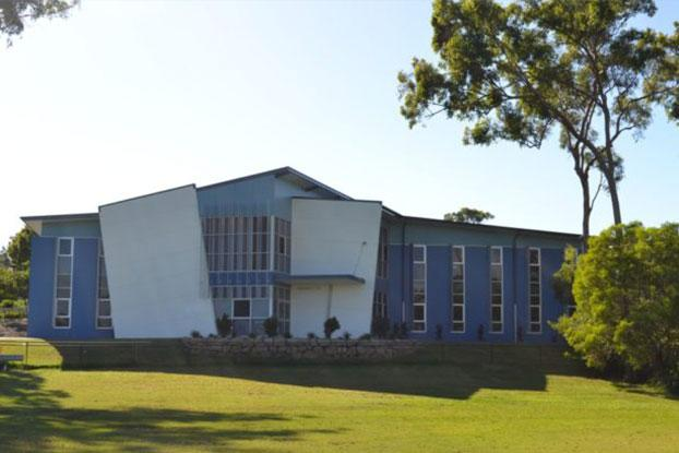 A large, modern concrete school building in blue tones with large exposed glass windows.