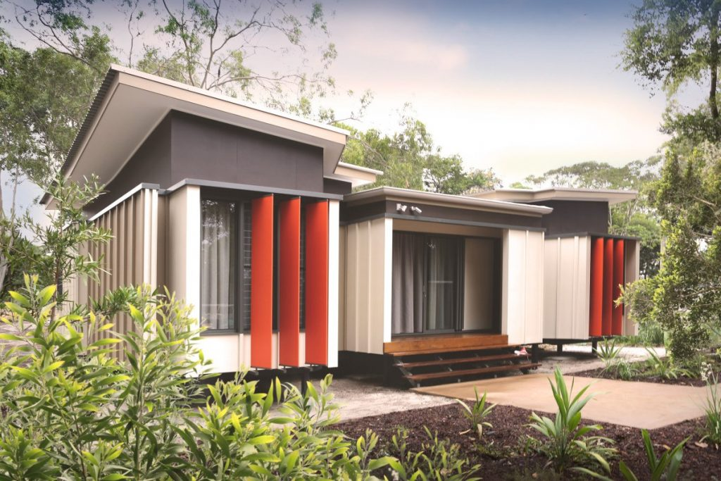 A modern residential building with raised foundations, timber decking and bright red louvres among neutral facades.